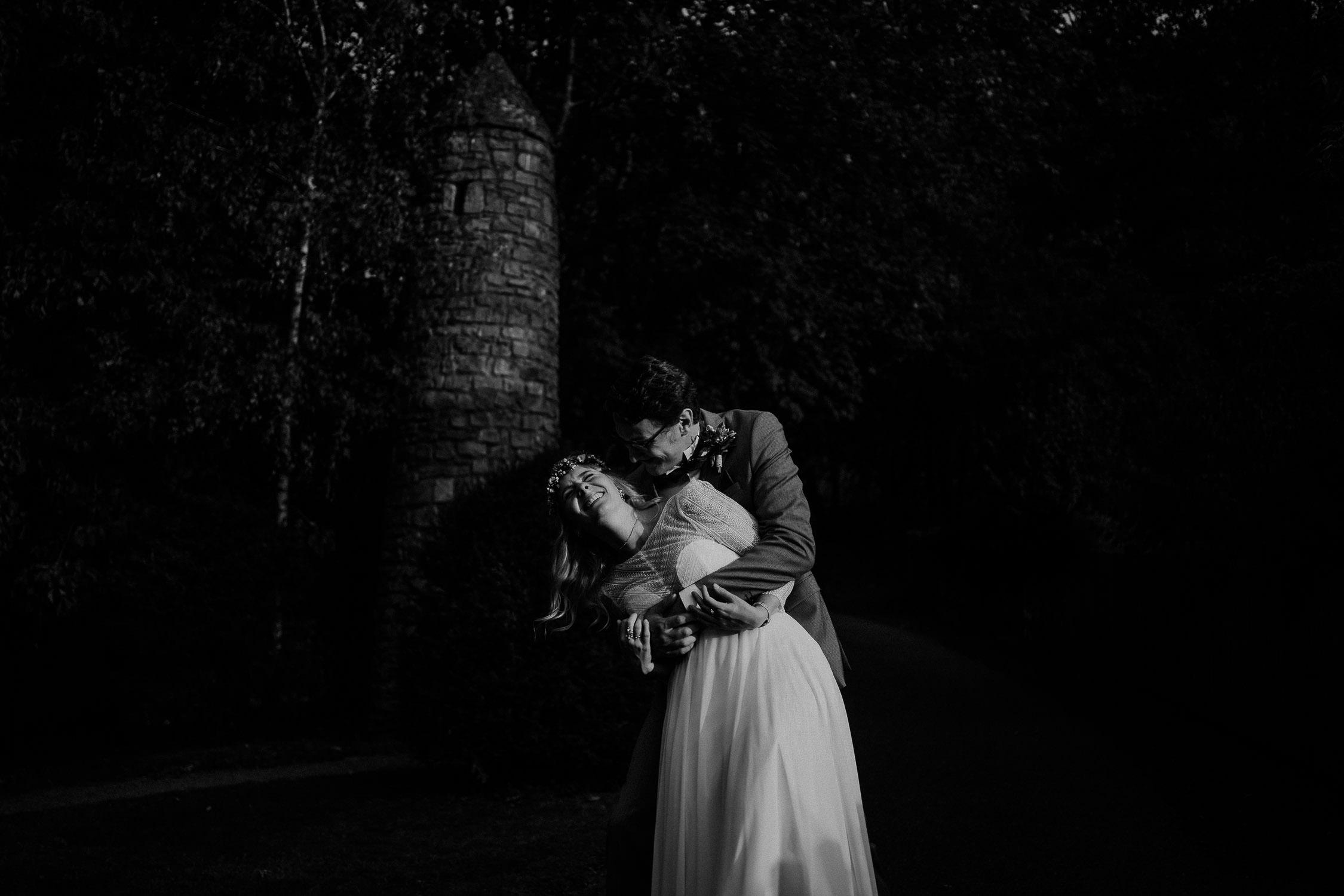 Portrait des Brautpaares in Schwarz Weiß. Fotografiert von Hochzeitsfotograf Axel Link. Die Braut lacht.