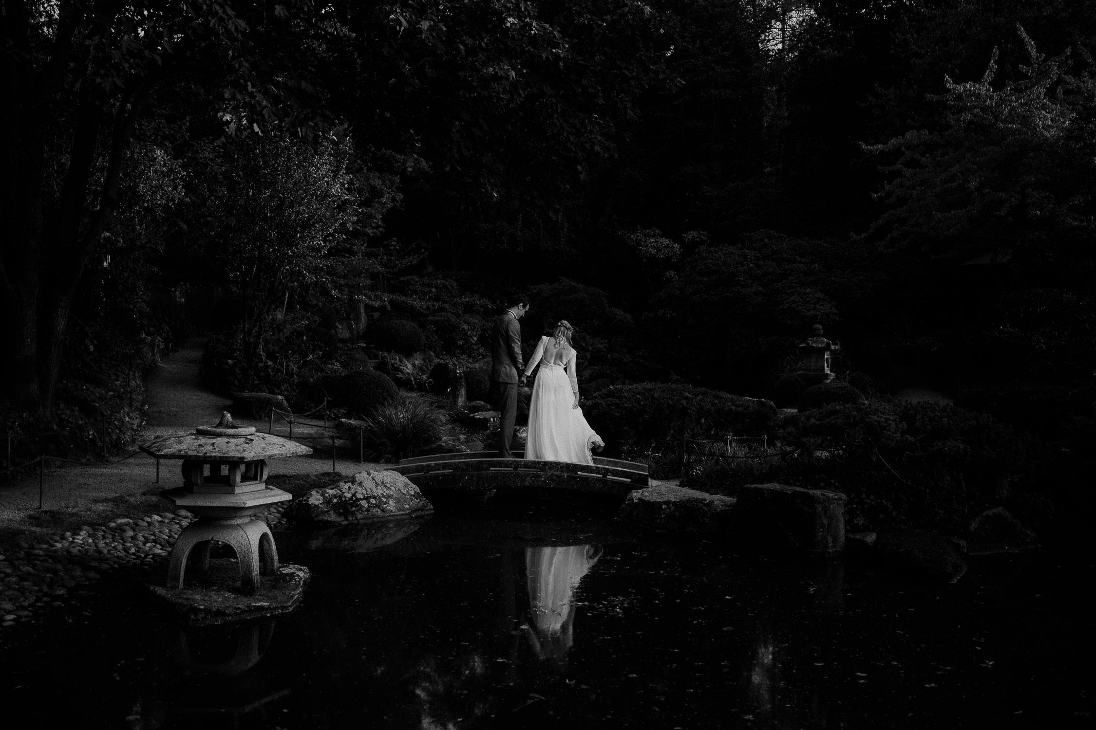 Portrait des Brautpaares in Schwarz Weiß. Fotografiert von Hochzeitsfotograf Axel Link. Das Brautpaar spiegelt sich im See.