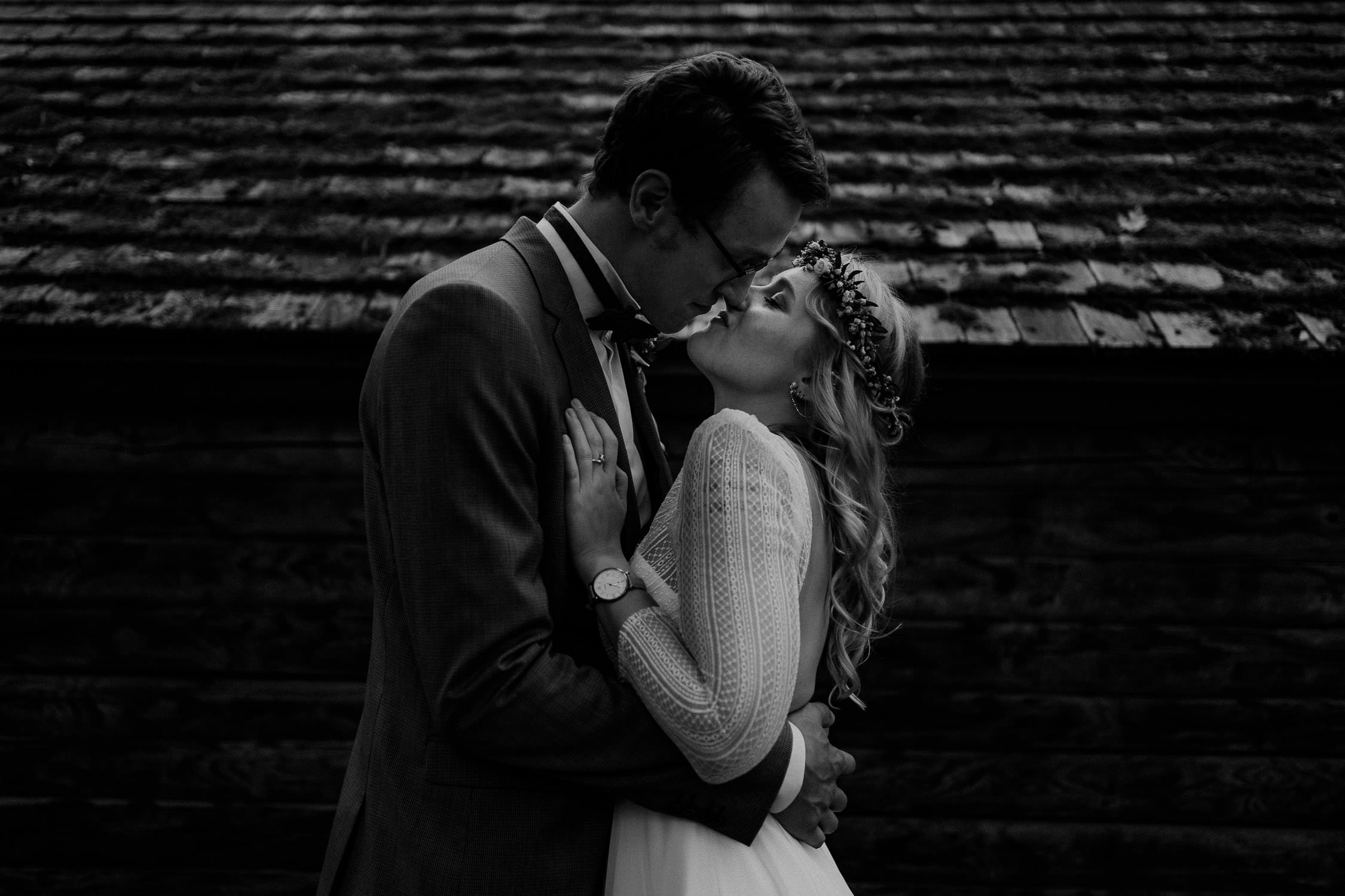 Portrait des Brautpaares in Schwarz Weiß. Fotografiert von Hochzeitsfotograf Axel Link. Brautpaar küsst sich.