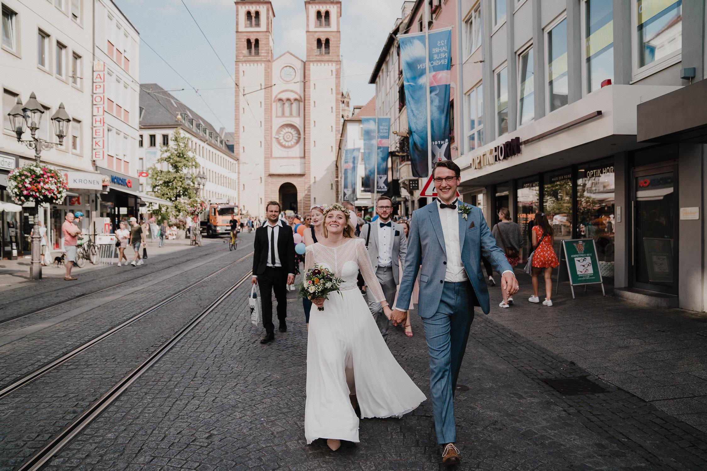 Das Brautpaar läuft in der Domstraße Wuerzburg. Fotografiert von Hochzeitsfotograf Axel Link