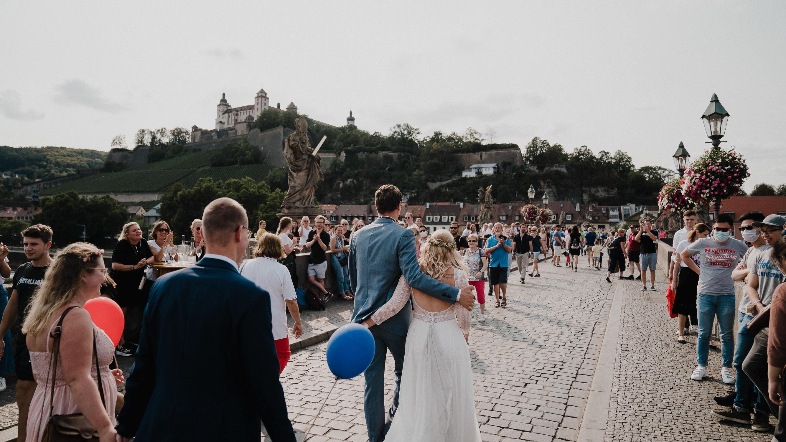 Das Brautpaar läuft über die Alte Mainbrücke in Wuerzburg. Die Festung Marienberg im Hintergrund. Fotografiert von Hochzeitsfotograf Axel Link