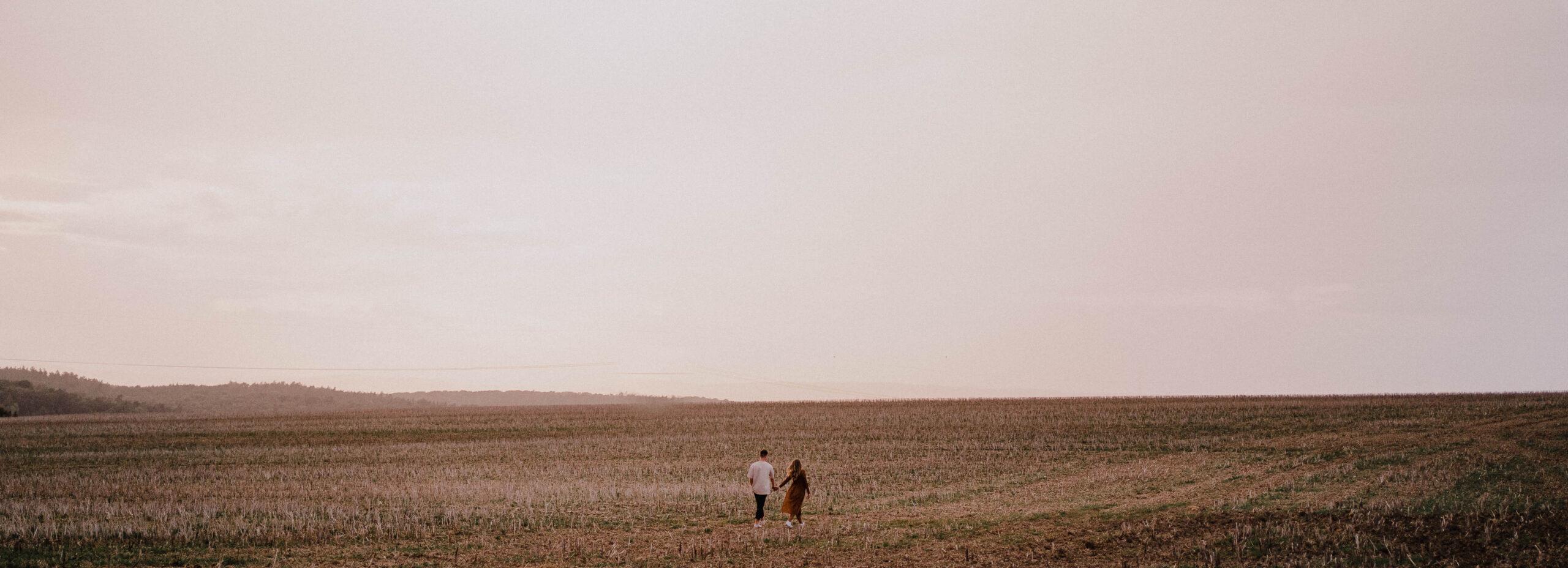 Pärchen läuft über ein Feld. Foto vom Hochzeitsfotogarf Axel Link aus Würzburg